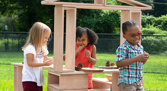 three kids playing in spring and building a clubhouse with hollow wooden blocks