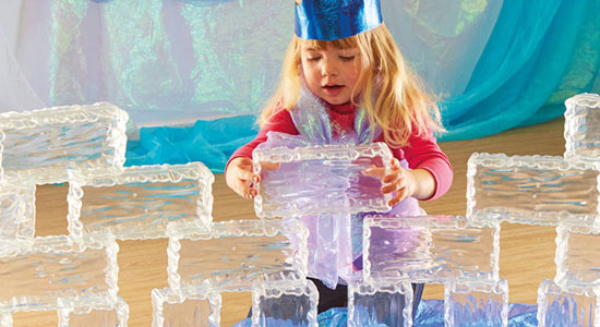 young girl building a wall with plastic ice blocks